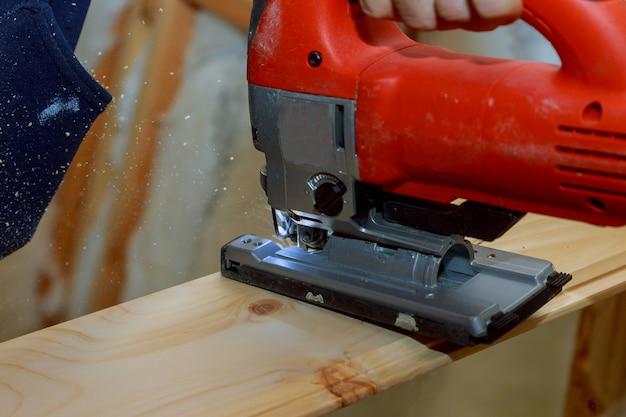 Sluit omhoog elektrische figuurzaag die een stuk van hout snijdt