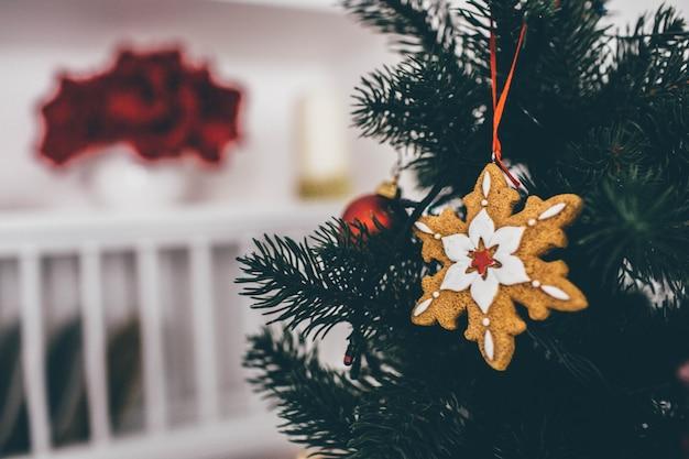 Sluit omhoog en knip de weergave van decoratie op kerstboom in sneeuwvlokvorm. kamer is op onscherpe achtergrond.