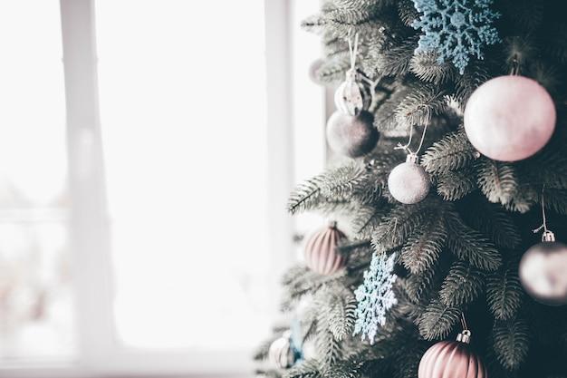 Sluit omhoog en knip de weergave van het versierde deel van de kerstboom klaar voor de tijd van het nieuwe jaar. roze en witte versieringen rondom de boom.