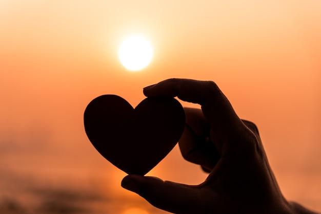 Sluit omhoog en silhouet van hand die rood hart houden tijdens zonsondergangachtergrond