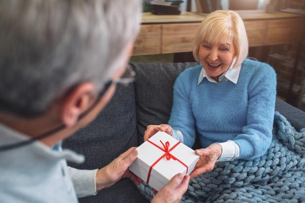 Sluit omhoog en snijd mening die van de oude man een gift geven aan haivrouw.