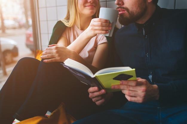 Sluit omhoog en snijd mening van een jongen en meisjeszitting in koffie dichtbij groot venster. ze drinkt wat koffie en geeft haar kopje om hem dit drankje te laten proberen. de jongeman houdt een boek vast.