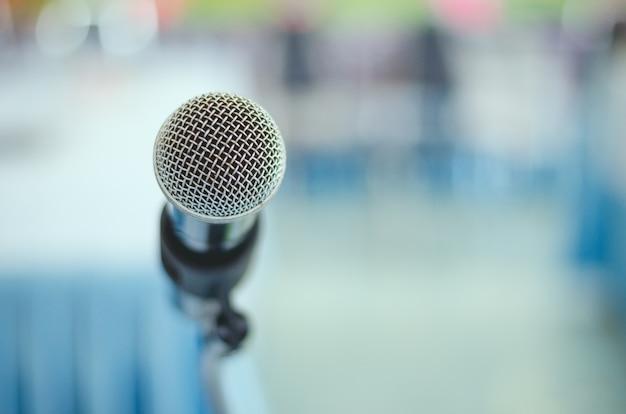Sluit omhoog enige microfoon in vergaderzaal met vage achtergrond
