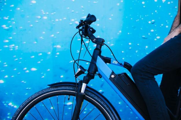 Sluit omhoog fietser op e-fiets met aquariumachtergrond