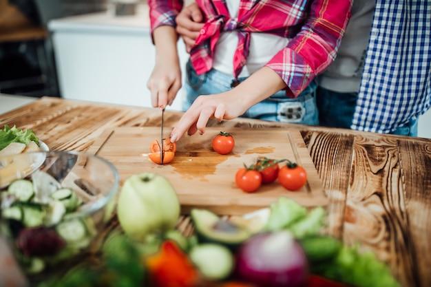 Sluit omhoog foto die van vrouwenhanden de tomaat snijden bij houten bureau. man blijft achter