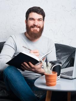 Sluit omhoog foto van de gelukkige mens die zijn jaar plannen en nieuwe doelstellingen stellen