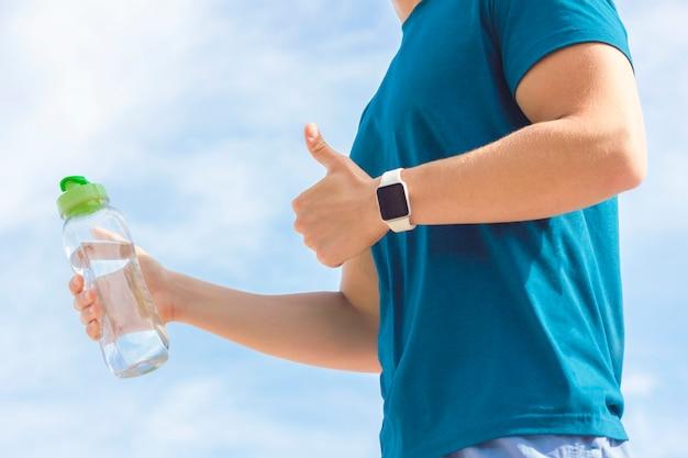 Sluit omhoog foto van de hand van de atleet met smartwatch, fles in hand water. onherkenbaar persoon, fit man loper tonen als gebaar, duim omhoog. gezonde sport actieve fitness levensstijl, gadgetconcept