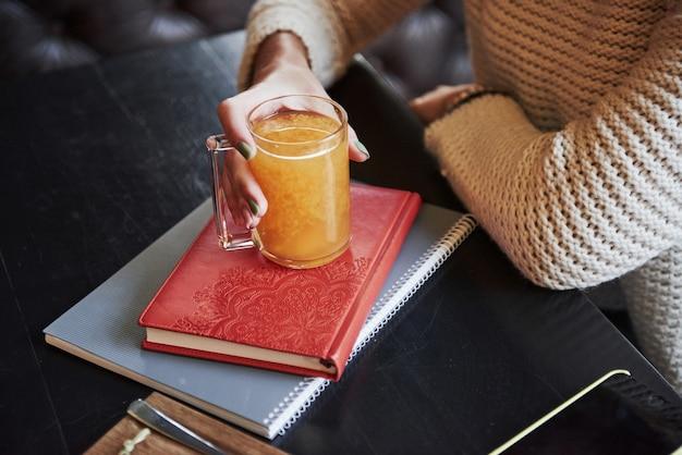 Sluit omhoog foto van de oranje drank die door vrouwenhand houdt en op het boek met rode dekking staat