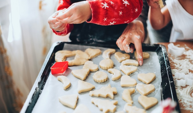Sluit omhoog foto van een familie die in vakantiekleren kerstmiscakes van verschillende vormen maken