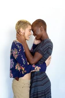 Sluit omhoog foto van een glimlachend mooi jong lesbisch paar van aangezicht tot aangezicht in studio