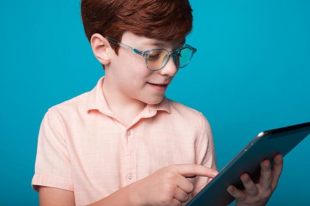 Sluit omhoog foto van een kaukasische gemberjongen die een bril draagt die een tablet op een blauwe studiomuur gebruikt