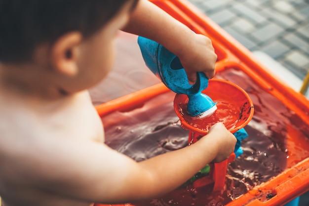 Sluit omhoog foto van een kaukasische jongen die buiten met water en plastic speelgoed speelt dat in backyad wordt uitgekleed