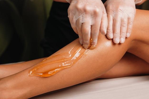 Sluit omhoog foto van een suikerbehandeling op benen die door een ervaren kuuroordspecialist wordt uitgevoerd