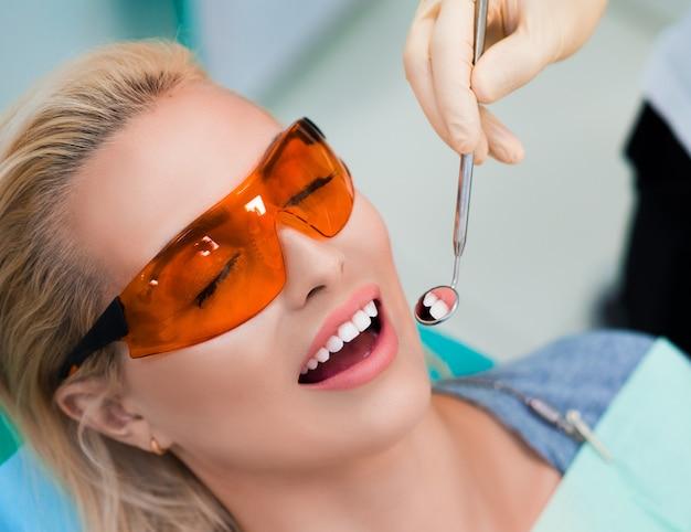 Sluit omhoog foto van een vrouw die aan de tandarts bezoeken.