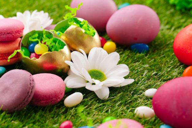 Sluit omhoog foto van gekleurde paaseieren en suikergoed op gras