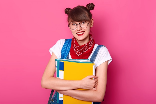 Sluit omhoog foto van gelukkige knappe student met document omslag die op rooskleurige muur wordt geïsoleerd, die t-shirt en overall dragen, klaar voor rust en het ontspannen zijn, bekijkend camera en het glimlachen.