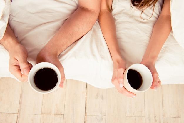 Sluit omhoog foto van handen van twee minnaars die kopjes met koffie houden