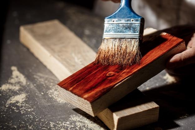 Sluit omhoog foto van het schilderen van hout in bruine kleur.