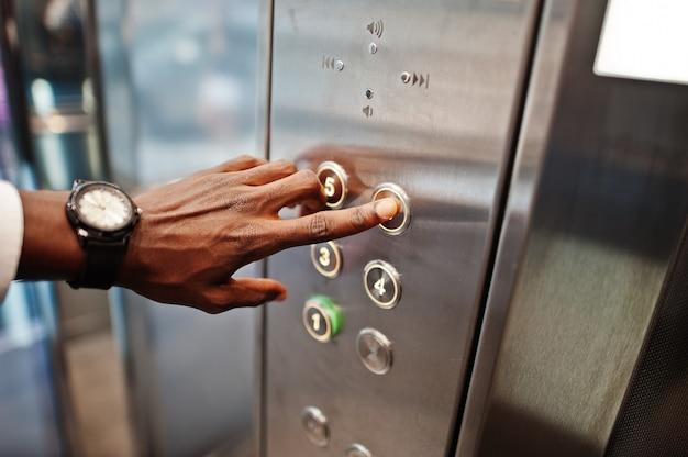 Sluit omhoog foto van mensenhand met horloges bij elavator of moderne lift, duwend knoop