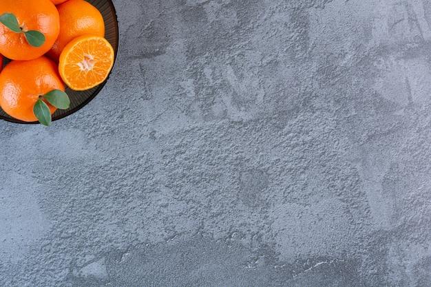 Sluit omhoog foto van organische mandarijnen op plaat over grijs.