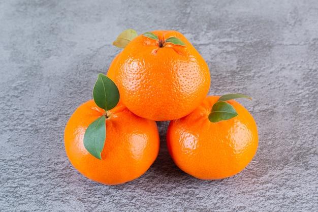 Sluit omhoog foto van organische mandarijnstapel op grijs.