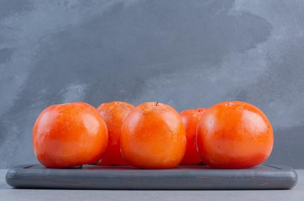 Sluit omhoog foto van rijp oranje dadelpruimfruit. op houten bord.