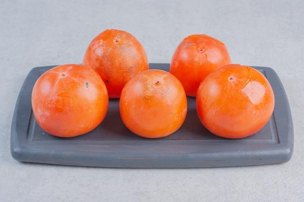 Sluit omhoog foto van rijp oranje dadelpruimfruit. verse persimmon op een houten bord.