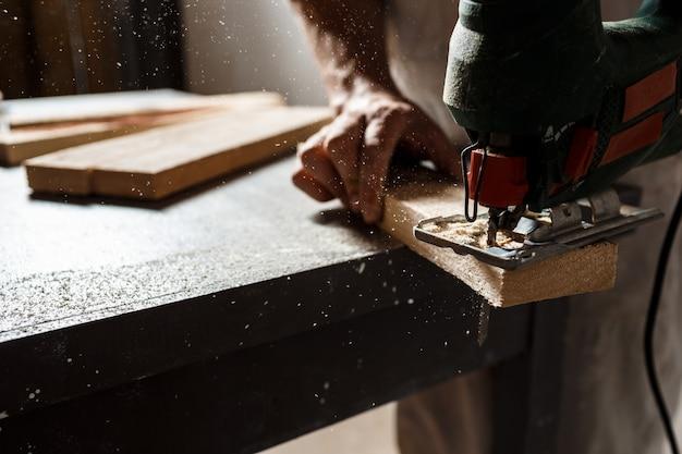Sluit omhoog foto van scherp hout met figuurzaag.