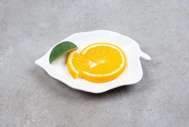 Sluit omhoog foto van sinaasappelplak met blad op witte plaat in bladvorm.