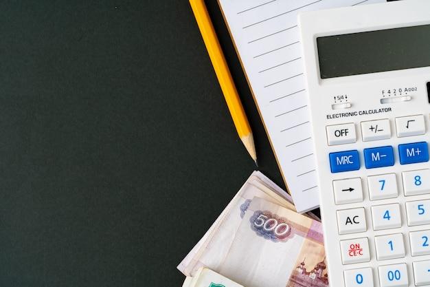 Sluit omhoog foto van stapel russische geldroebels met calculator