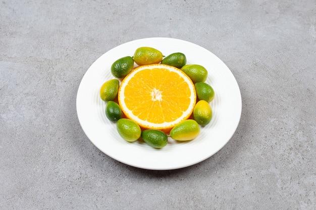 Sluit omhoog foto van stapel van kumquats met oranje plak op witte plaat.