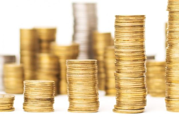 Sluit omhoog foto van stapels van gouden muntstukken die stijgende richting met vele muntstukken tonen