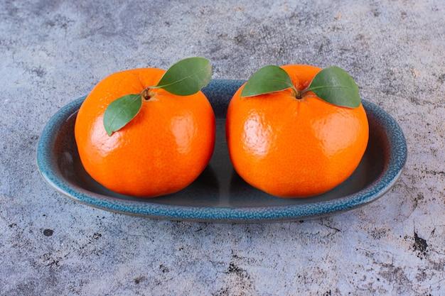 Sluit omhoog foto van twee verse mandarijnen op plaat over grijs.