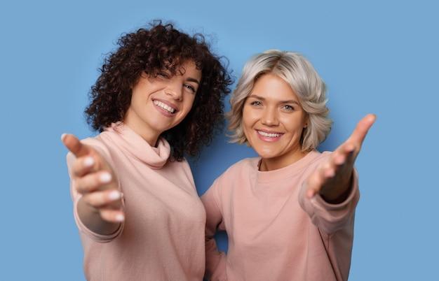 Sluit omhoog foto van twee vrouwen met krullend haar die bij camera glimlachen en gebaren met palmen op een blauwe studiomuur uitnodigen
