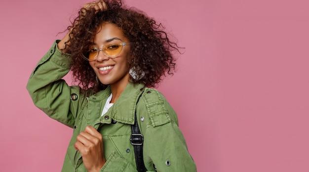Sluit omhoog foto van verbazend krullend afrikaans meisje op roze achtergrond. het dragen van groene trendy jas.