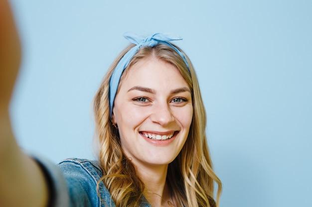 Sluit omhoog foto van vrolijke persoon die ok teken maken die gele die t-shirt dragen over blauwe achtergrond wordt geïsoleerd