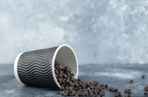 Sluit omhoog fotostapel van kleine chocolade op grijze achtergrond.