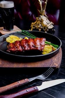 Sluit omhoog gastronomisch hoofdgerecht met geroosterde varkensvleesrib en gebraden aardappels op zwarte pan. geserveerd op een houten bord