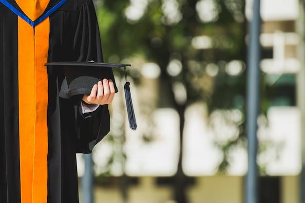 Sluit omhoog gediplomeerde die een hoed houden. concept succes onderwijs op universiteit