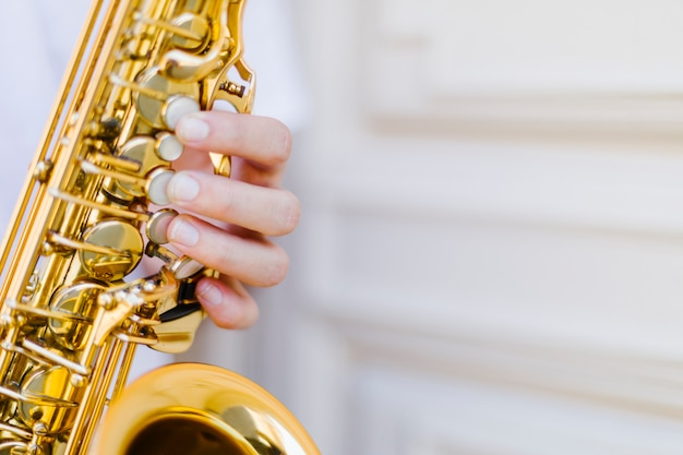 Sluit omhoog gehouden saxofoon met vage achtergrond