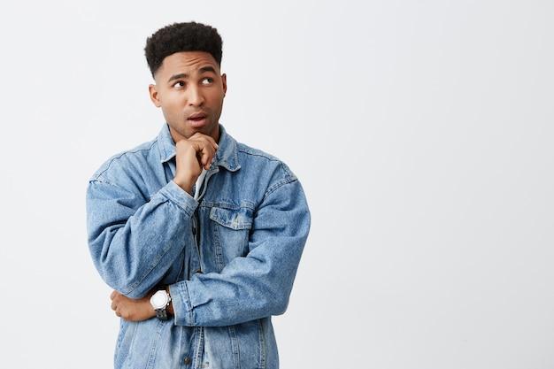 Sluit omhoog geïsoleerd portret van jonge mooie donkere man met afrokapsel in denimjasje wat betreft kin met hand, kijkend opzij met nadenkende uitdrukking. kopieer ruimte