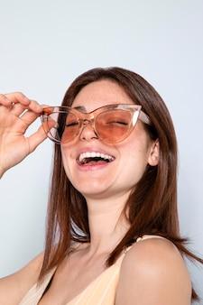 Sluit omhoog gelukkige vrouw die zonnebril draagt