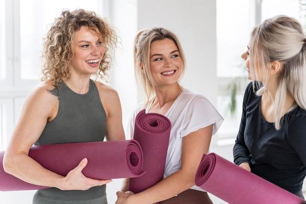 Sluit omhoog gelukkige vrouwen die yogamatten houden