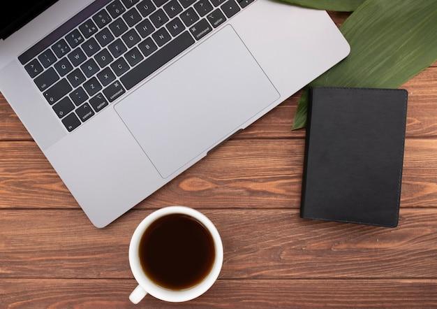 Sluit omhoog geopende laptop met koffie en notitieboekje op oud houten bureau. plat lag stijl. bovenaanzicht