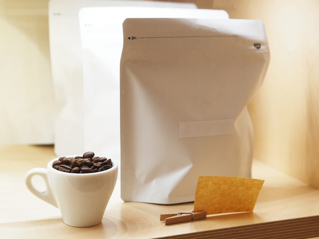 Sluit omhoog geroosterde koffieboon in witte kop en document ritssluitingszakken