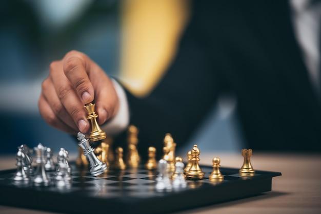 Sluit omhoog geschoten gouden schaak om het doden van zilveren koningsschaak op wit en zwart schaakbord te verslaan voor de winnaar en het verliezersconcept van de bedrijfsuitdagingscompetitie
