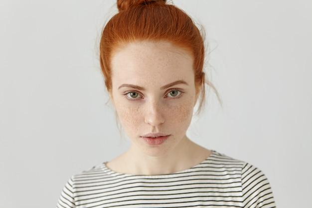 Sluit omhoog geschoten van charmante jonge roodharige europese vrouw met sproeten en haarbroodje kijkend met ernstige gelaatsuitdrukking, gekleed in toevallige gestreepte bovenkant. mensen en levensstijl concept