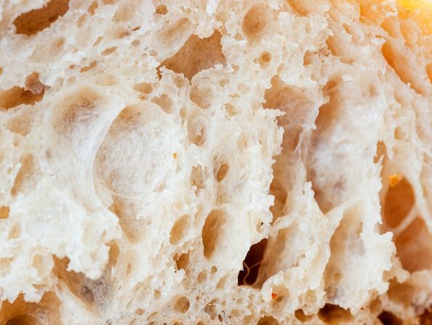 Sluit omhoog geschoten van de witte plak van het zuurdesembrood. macro van brood segment textuur. lekker vers brood, close-up voor achtergrond