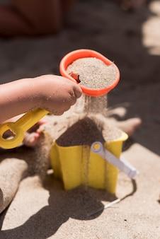 Sluit omhoog geschoten van emmerhoogtepunt van zand