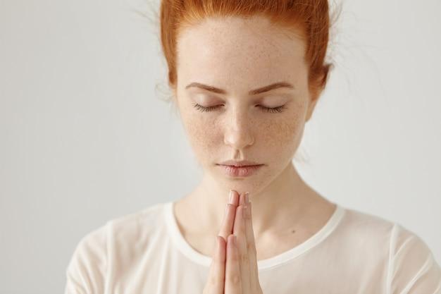 Sluit omhoog geschoten van godsdienstige jonge gembervrouw in witte blouse die mediteren of bidden houdend gesloten ogen en samen gedrukte handen, hopend op het beste. mensen, religie, spiritualiteit, gebed